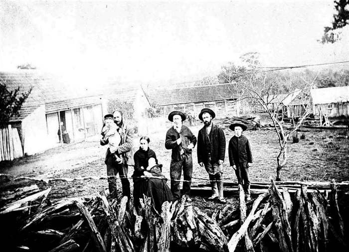 Image - Photo. Three men with one holding a baby, a young boy and a young mother sitting down holding a baby in the rear of Shepherd's Run farm.