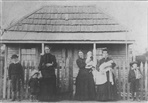 Image - Photo. Two ladies holding infants, one lady holding a child with one young boy on one side and the other young boy with a sling on his left arm, all standing in front of Shepherd's Run.
