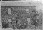 Mary, William and Sam Dennis standing in front of 36 Walker Street, Northcote
