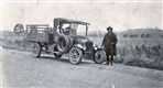 Image - Photo. A.J. Dickson standing on the side of a road next to a motor vehicle.